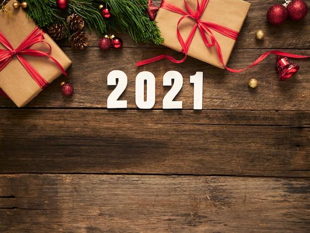 Fundo de natal de ano novo 2021 com caixas de presente, galhos de árvores de abeto e decorações em fundo rústico de madeira escura