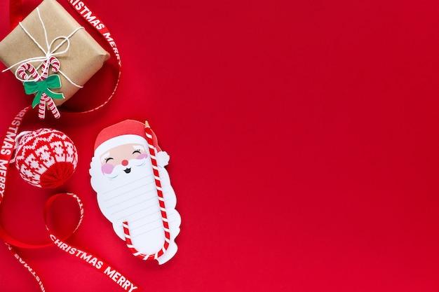 Fundo de natal de ano novo. caderno do papai noel, lápis para lista de desejos, caixa de presente em fundo vermelho com espaço de cópia, layout
