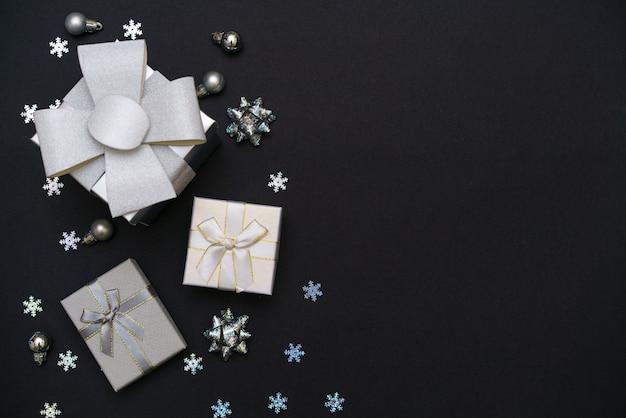 Fundo de natal de caixas de presente de flocos de neve decorativos de cor prata em fundo preto escuro.