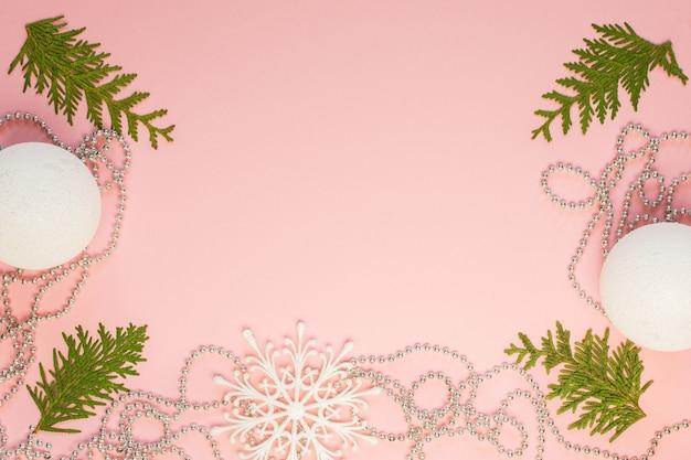 Fundo de natal de férias, ramos de pinheiro e contas decorativas de prata, flocos de neve brancos e bolas de natal em fundo rosa, vista de cima plana