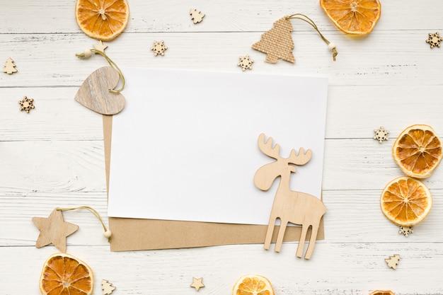 Fundo de natal de laranjas secas, decorações de natal e cartão branco vazio para saudações em uma mesa de madeira. estrelas, corações e alces. vista do topo. copyspace.