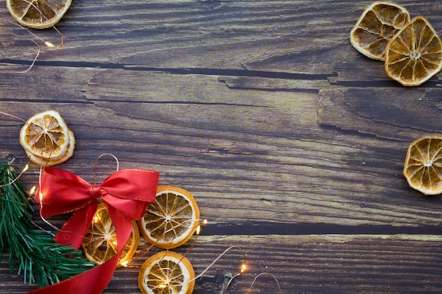 Fundo de natal de laranjas secas, galho de pinheiro, laço vermelho e guirlanda em uma mesa de madeira