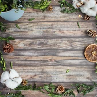 Fundo de natal de madeira com buxo, algodão, cones de abeto, laranjas e guirlanda