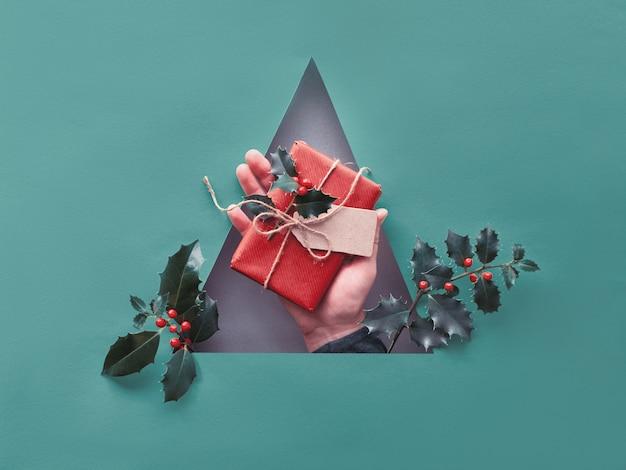 Fundo de natal de papel turquesa tonificado com furo triangular com a mão segurando o presente de natal embrulhado com etiqueta de papelão e galhos de azevinho com bagas vermelhas.