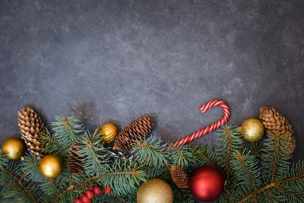 Fundo de natal de ramos de abeto, bolas de natal e doces, pinhas.