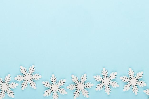 Fundo de natal. decorações de neve branca em um fundo rosa.