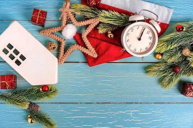 Fundo de natal em forma de moldura com um relógio e um chapéu de papai noel em uma mesa de madeira azul.