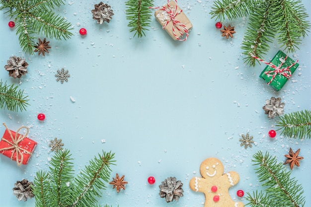 Fundo de natal feito de galhos de árvores de abeto, decorações, frutas, pão de gengibre em fundo azul