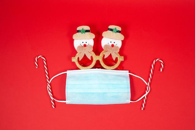 Fundo de natal festivo com máscara facial, pirulito e óculos engraçados. novo conceito normal de natal.