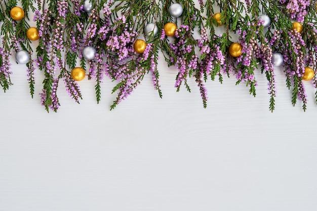 Fundo de natal. fronteira de urze comum com decoração em fundo branco. copie o espaço, vista superior.