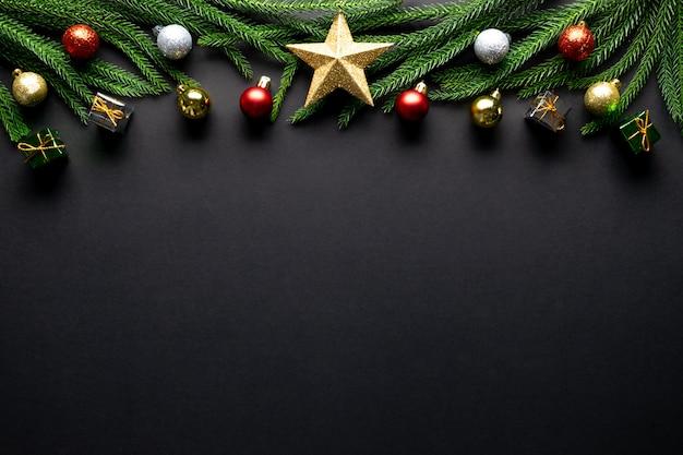 Fundo de natal. galhos de árvore do abeto, decorações vermelhas em fundo preto
