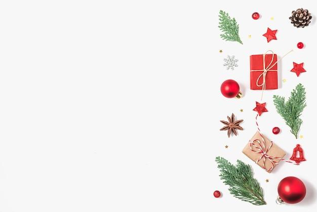 Fundo de natal. galhos de árvores de abeto, caixas de presente, decorações vermelhas, pinhas em fundo branco. natal, inverno, conceito de ano novo. postura plana. vista de cima com espaço de cópia