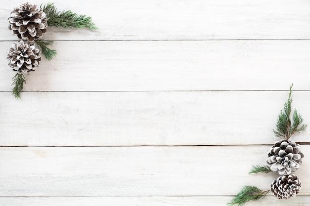 Fundo de natal. moldura de natal feita de folhas de abeto e cones de pinheiro decoração de elementos rústicos em placa de madeira branca. layout plano criativo, design de vista superior