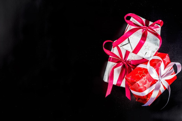 Fundo de natal para cartão, com galho de árvore de natal e caixas de presentes com fitas, na vista superior de fundo preto copie o espaço para texto