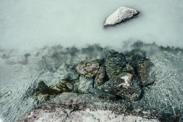 Fundo de natureza com pedras cobertas de musgo na água prateada do rio da montanha areia prateada