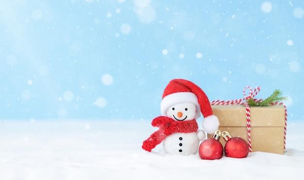Fundo de neve de natal com caixa de presente de boneco de neve e enfeites de natal