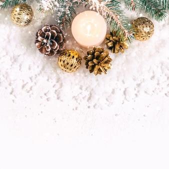 Fundo de neve de natal. vela acesa, galhos de pinheiro e cones