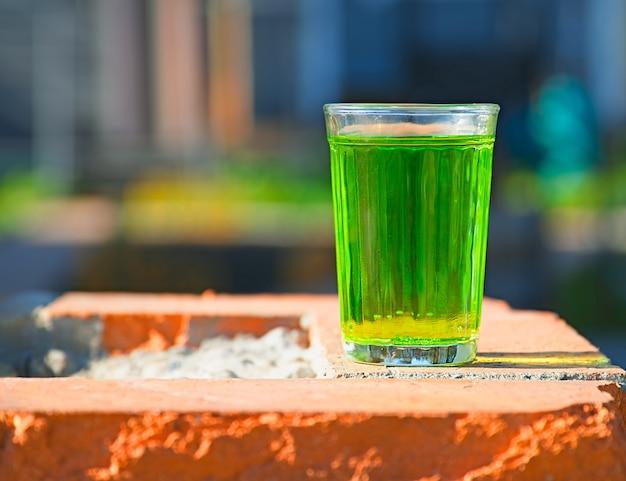 Fundo de objeto de vidro de refrigerante com ácido verde
