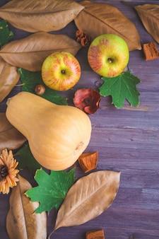 Fundo de outono. abóboras deixa maçãs em um fundo de madeira