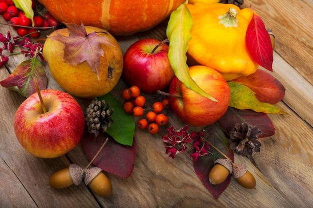 Fundo de outono com abóbora amarela, maçãs, pêra, folhas coloridas