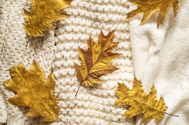 Fundo de outono com camisolas quentes. pilha de roupas de malha com folhas de outono, conceito outono-inverno.