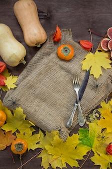Fundo de outono com folhas amarelas, figos, caquis e abóboras.