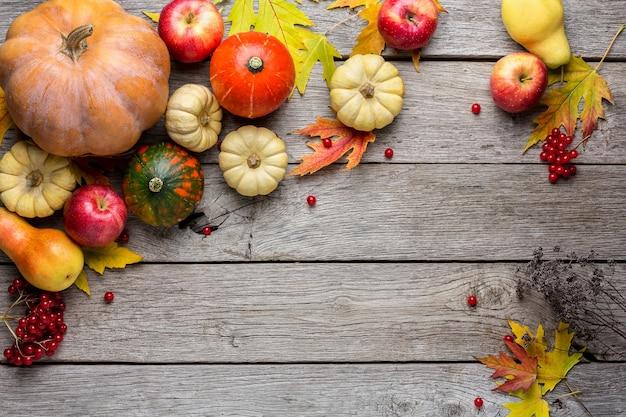 Fundo de outono com folhas de bordo amarelas e abóboras. quadro de colheita de outono em madeira envelhecida.
