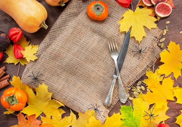 Fundo de outono com folhas de bordo amarelas, outono frutas e vegetais. conceito de halloween.