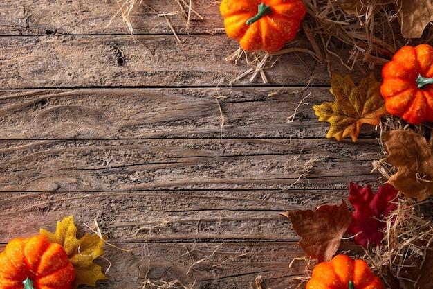 Fundo de outono com folhas e abóboras em fundo de madeira