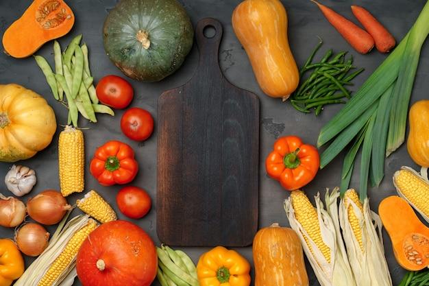 Fundo de outono com legumes frescos e tábua de madeira