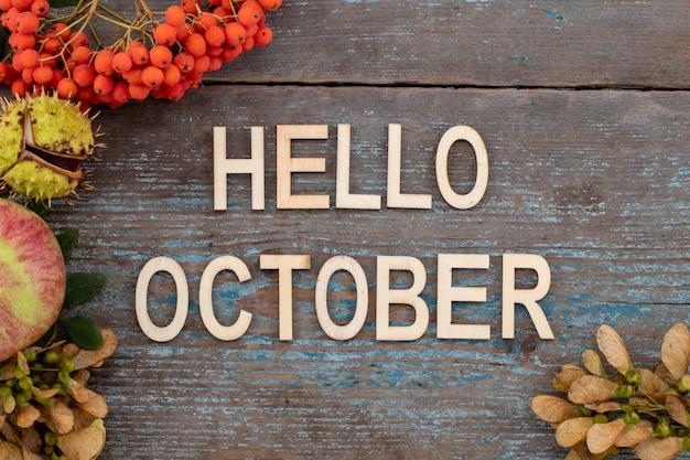 Fundo de outono com o texto - olá outubro na velha mesa de madeira.
