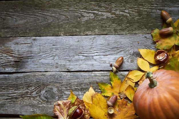 Fundo de outono de ação de graças, superfície de madeira escura com abóboras, folhas murchas, bolotas e castanhas, foco seletivo