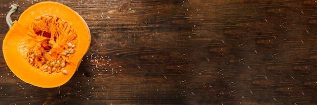 Fundo de outono. dia de ação de graças. metade de abóbora laranja na mesa de madeira marrom.