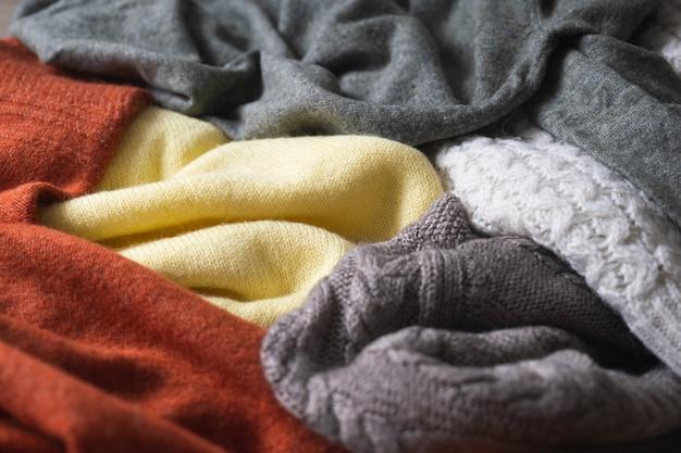 Fundo de outono em cores quentes com uma variedade de blusas de malha de lã ou mantas.
