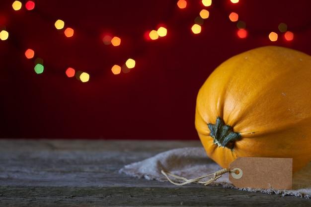 Fundo de outono em uma superfície de madeira escura, abóbora amarela em um fundo de luzes desfocadas, foco seletivo