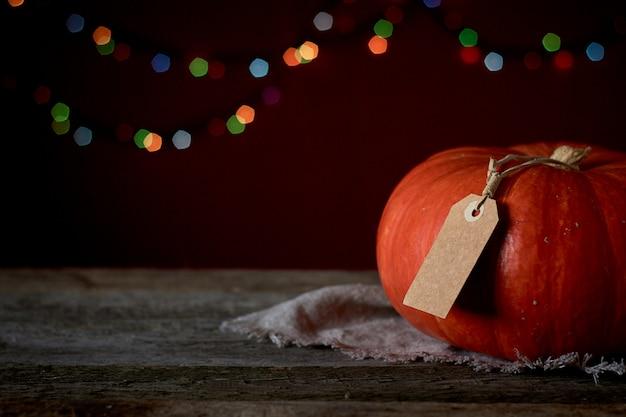 Fundo de outono em uma superfície de madeira escura, abóbora laranja em um fundo de luzes desfocadas, foco seletivo