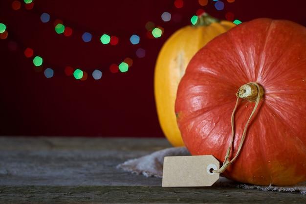 Fundo de outono em uma superfície de madeira escura, duas abóboras em um fundo de luzes desfocadas, foco seletivo