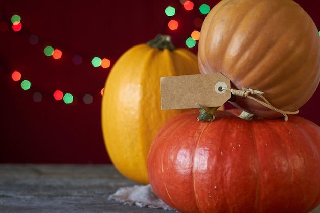 Fundo de outono em uma superfície de madeira escura, três abóboras em um fundo de luzes desfocadas, foco seletivo
