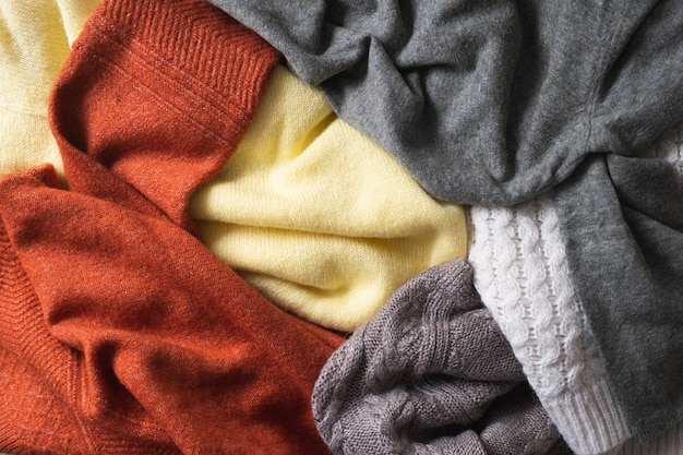 Fundo de outono ou inverno com suéteres quentes pilha de roupas quentes de malha