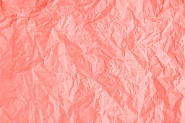 Fundo de papel amassado da textura no coral na moda.