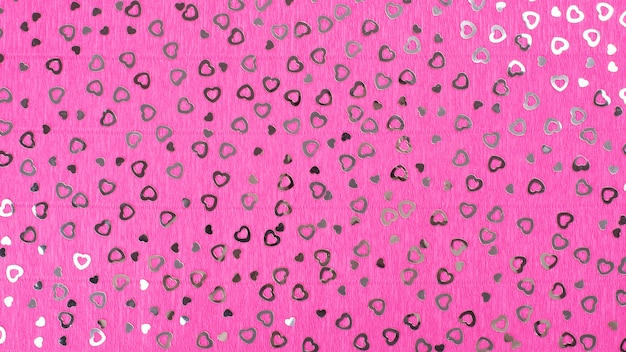 Fundo de papel crepe rosa brilhante com lantejoulas de corações.