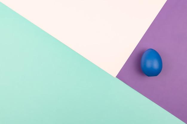 Fundo de papel geométrico abstrato de cores rosa pastel e roxas com ovo de páscoa azul. copie o espaço para o design.