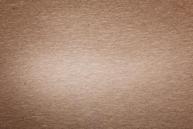 Fundo de papelão marrom com um ponto claro no meio
