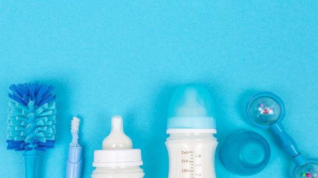 Fundo de papinha com mamadeiras com leite e acessórios de escova de mamadeira na mesa azul, vista de cima, espaço de cópia do quadro