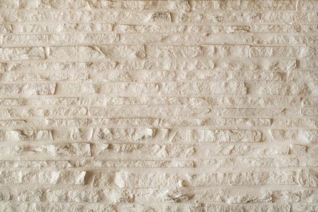 Fundo de parede texturizado branco com pedras.