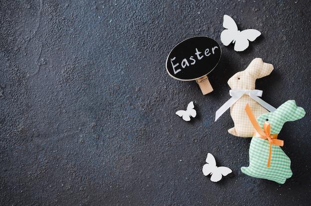 Fundo de páscoa com coelho decorativo, borboletas e inscrição páscoa.