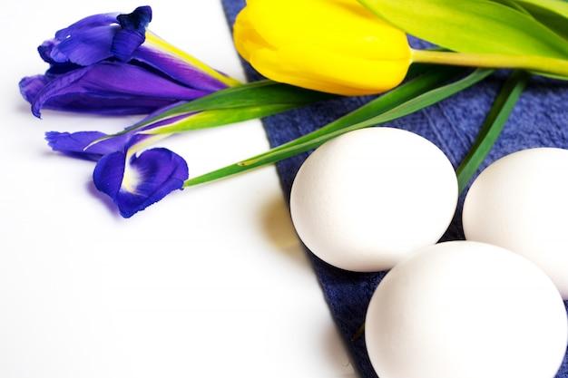 Fundo de páscoa com ovos brancos e flores da primavera