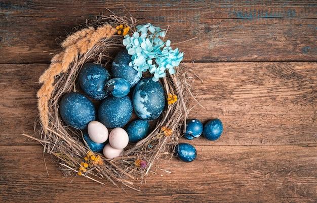 Fundo de páscoa com ovos de codorna e galinha azul em fundo de madeira.