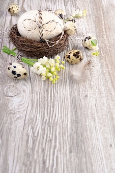 Fundo de páscoa com ovos e flores na madeira, espaço de texto