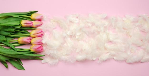 Fundo de páscoa com tulipas cor de rosa, penas brancas